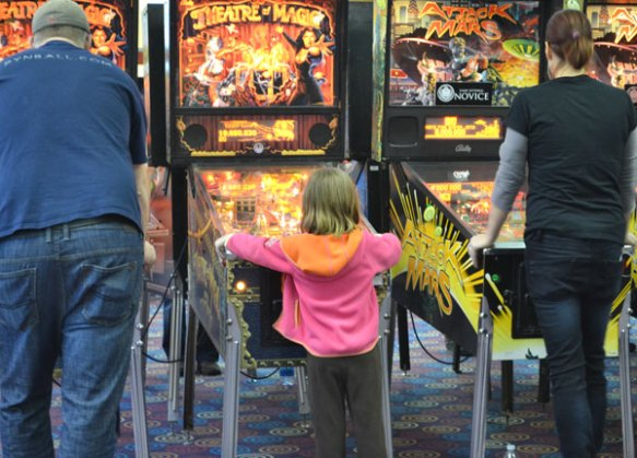 little girl plays pinball