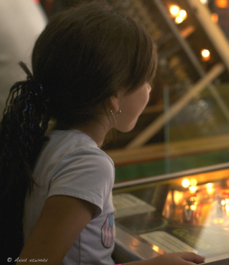 girl plays pinball