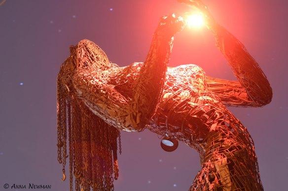 giant burning man sculpture at night