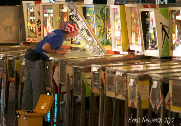 volunteer repairs pinball machine at pacific pinball expo 2012